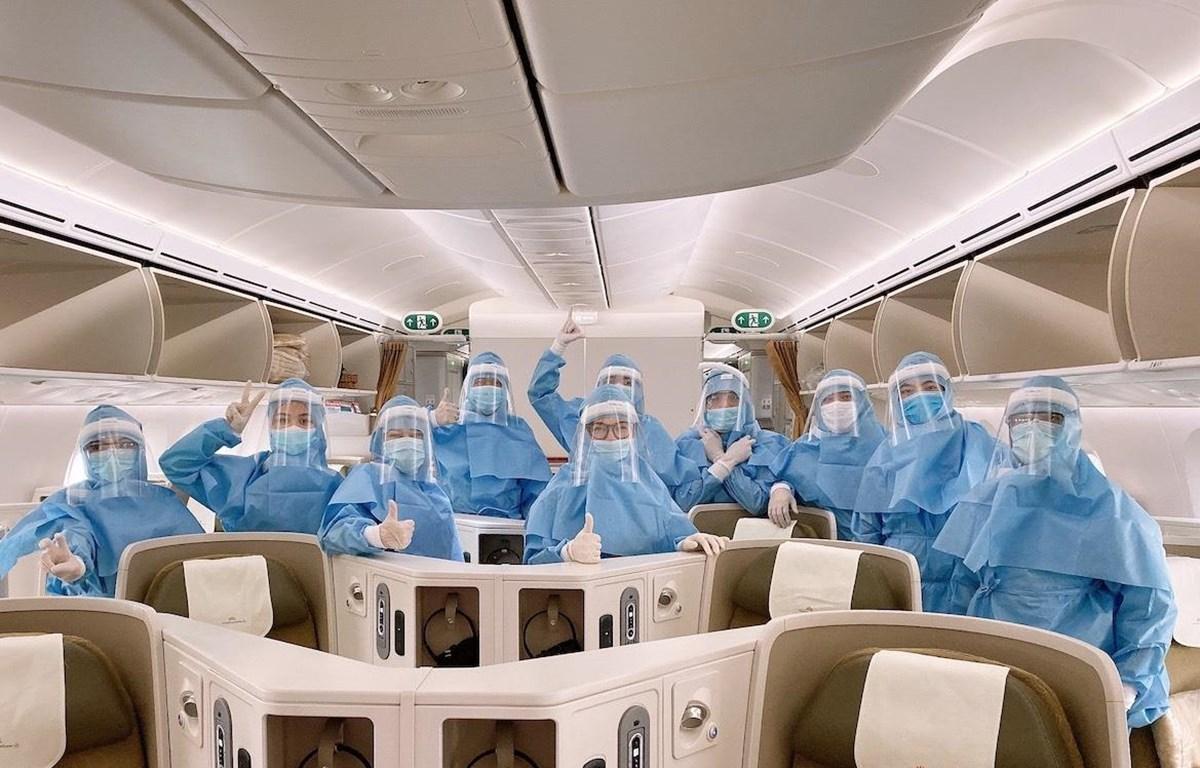 Các phi công, tiếp viên mặc trang phục bảo hộ trước khi thực hiện chuyến bay đến châu Âu. (Ảnh: VNA)