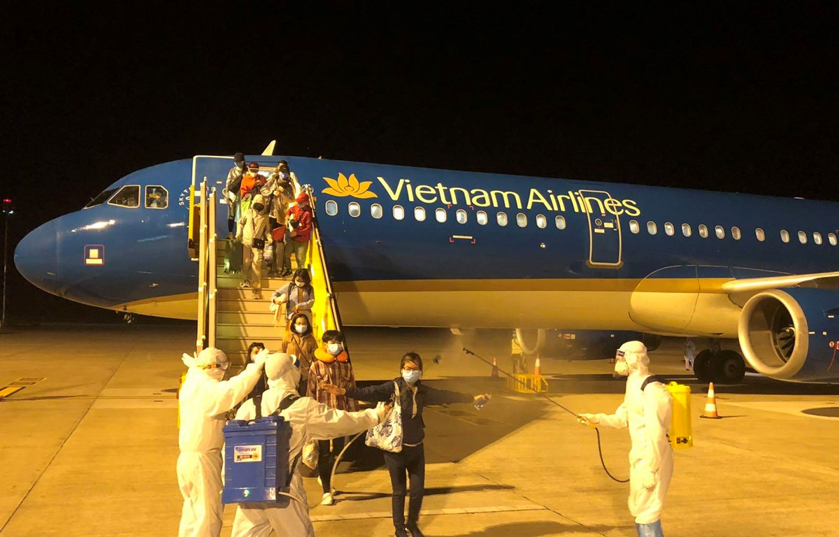 Phun khử khuẩn toàn bộ hành khách sau khi bước xuống máy bay và sau đó được đưa đi cách ly tập trung nhằm phòng chống COVID-19. (Ảnh: CTV/Vietnam+)