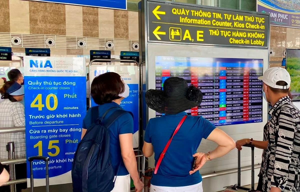 Hành khách theo dõi thông tin chuyến bay tại màn hình FIDS tại sân bay Nội Bài. (Ảnh: Văn phòng Cảng hàng không Nội Bài)
