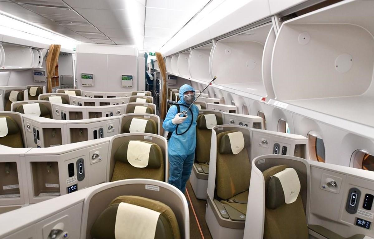 Vào cuối ngày khai thác, máy bay Vietnam Airlines vẫn được phun khử khuẩn tồn lưu qua đêm bởi đơn vị y tế chức năng. (Ảnh: Anh Tuấn/Vietnam+)