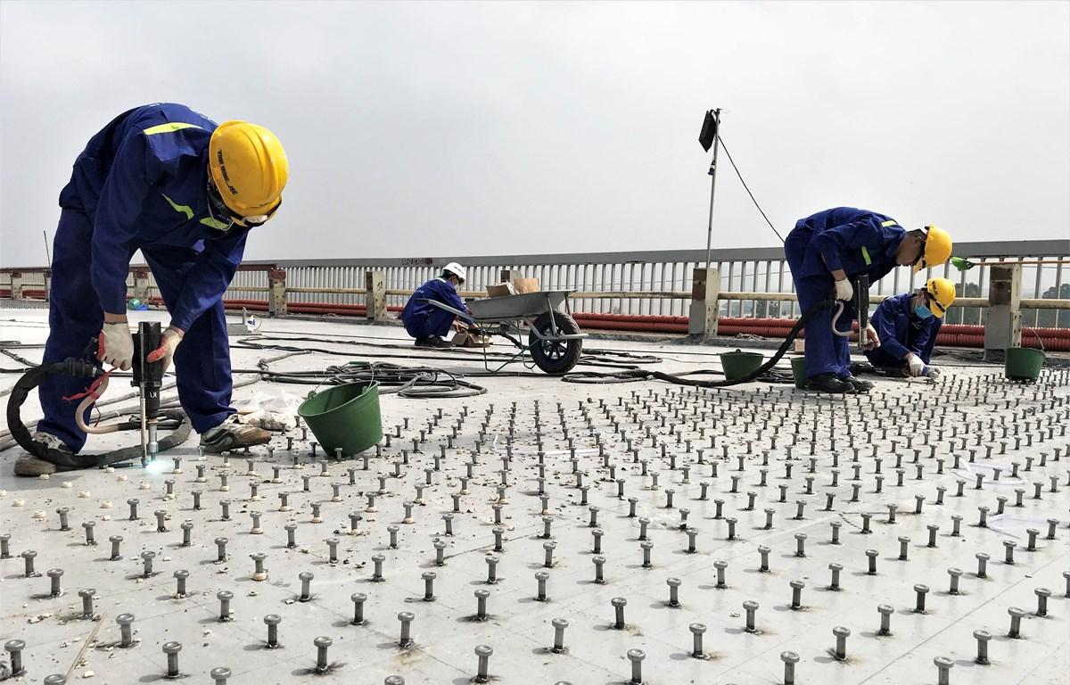 Công nhân tiến hành hàn đinh neo để tạo liên kết giữa bản mặt thép hiện tại và bê tông siêu tính năng UHPC nhằm tăng cường kết cấu chịu lực của mặt cầu Thăng Long. (Ảnh: Việt Hùng/Vietnam+)