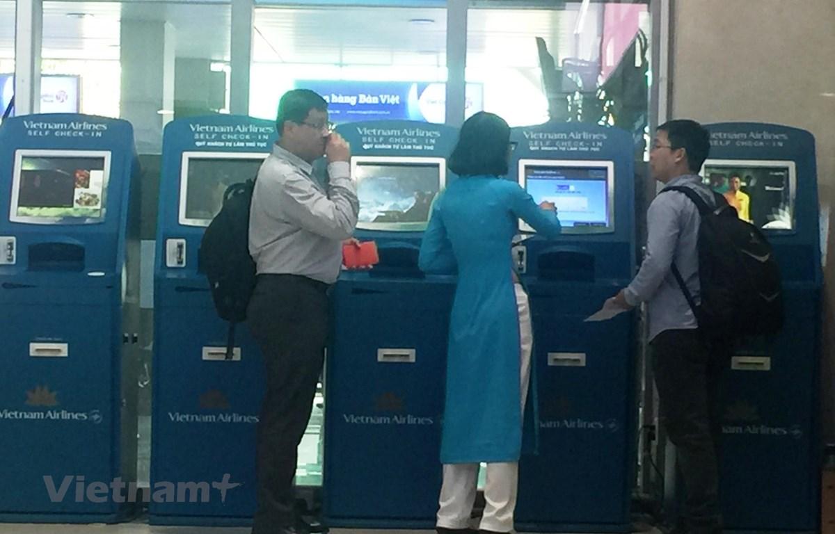 Hành khách làm dịch vụ thủ tục trực tuyến vé máy bay tại quầy Kios Vietnam Airlines ở một số sân bay. (Ảnh: Việt Hùng/Vietnam+)