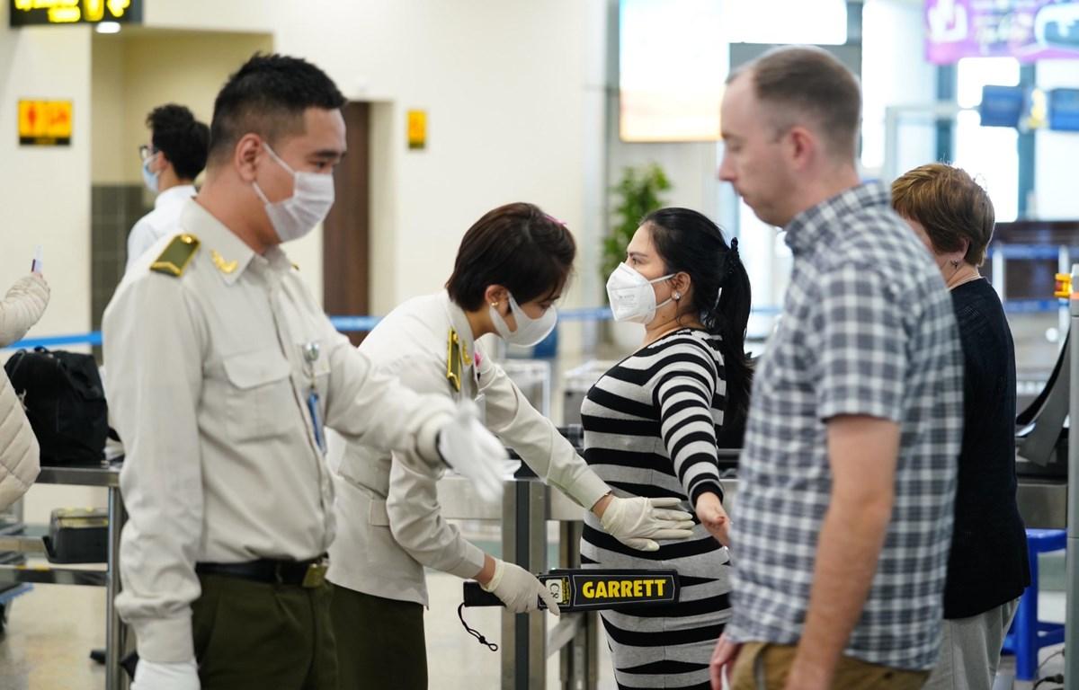 Nhân viên an ninh hàng không kiểm soát hành khách làm thủ tục chuyến bay. (Ảnh: CTV/Vietnam+)