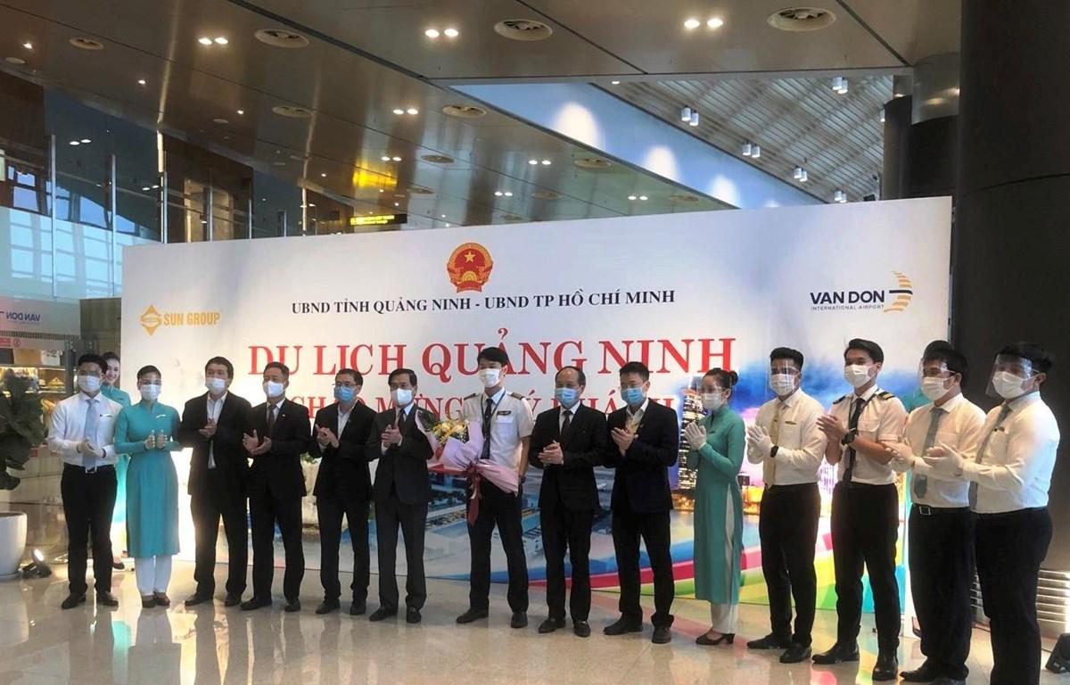 Lãnh đạo tỉnh Quảng Ninh và Vietnam Airlines tặng hoa cho phi hành đoàn chuyến bay Thành phố Hồ Chí Minh và Vân Đồn. (Ảnh: CTV/Vietnam+)