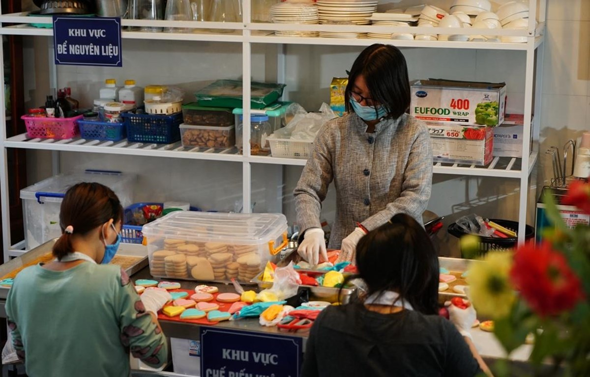 Chị Đặng Thị Hương, thành viên sáng lập HopeBox đang hướng dẫn cách làm bánh. (Ảnh: CTV/Vietnam+)