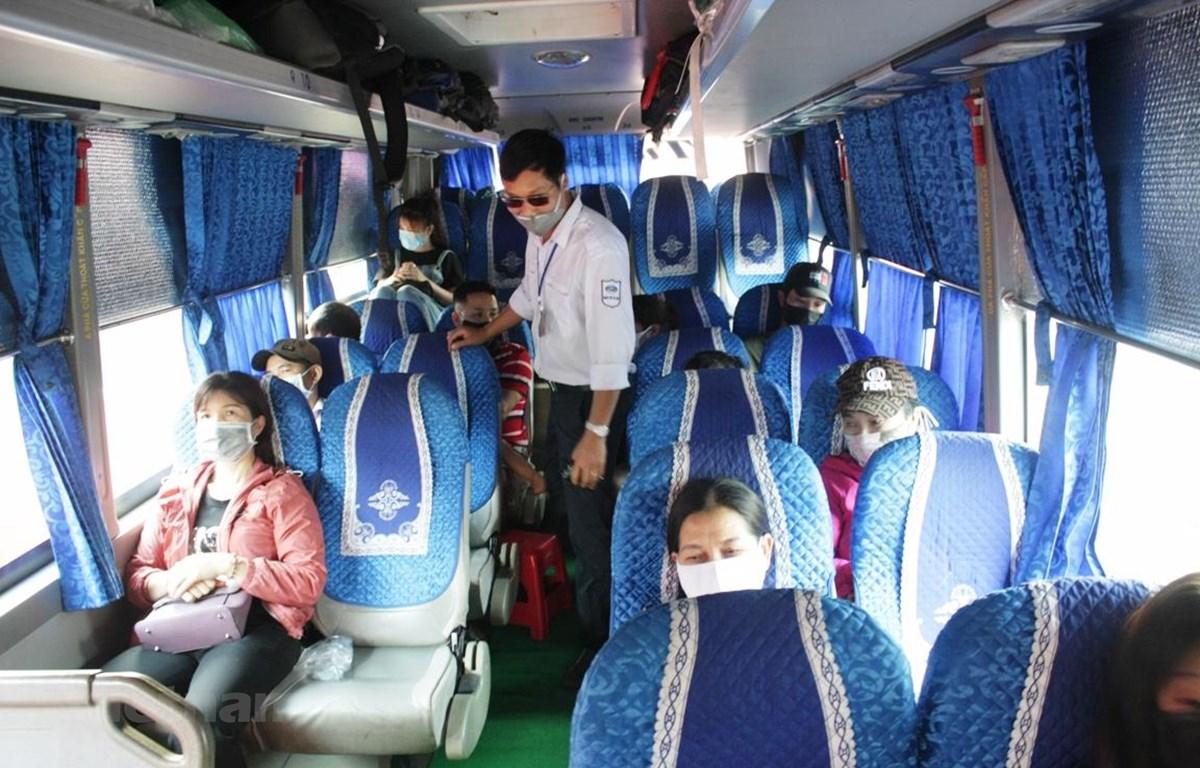 Nhân viên bến xe kiểm tra hành khách đeo khẩu trang, đảm bảo giãn cách theo đúng quy định về phòng chống dịch COVID-19. (Ảnh: Việt Hùng/Vietnam+)