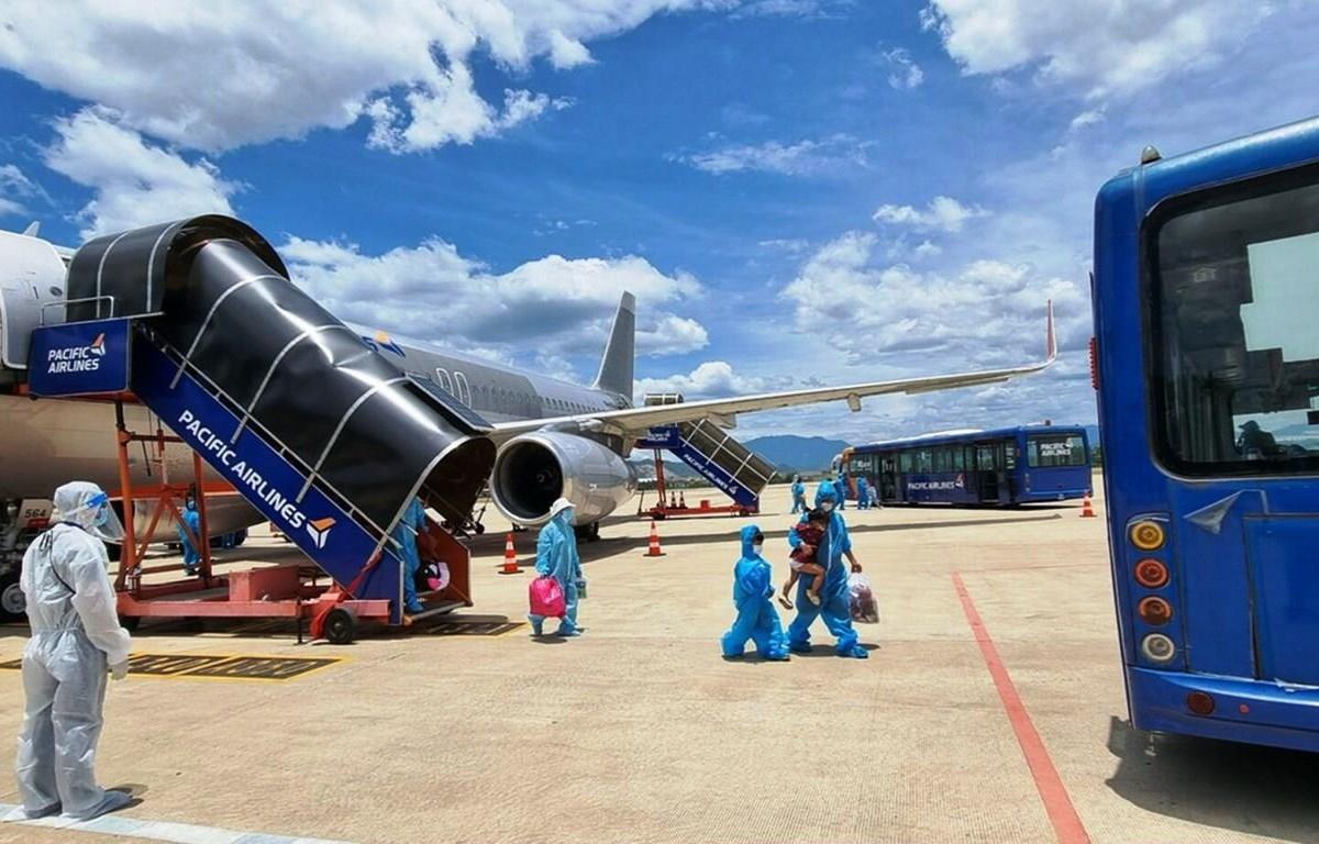Hành khách Quảng Nam xuống sân bay Đà Nẵng và được bố trí đưa về cách ly tập trung, bảo đảm quy trình khép kín phòng chống dịch. (Ảnh: CTV/Vietnam+)