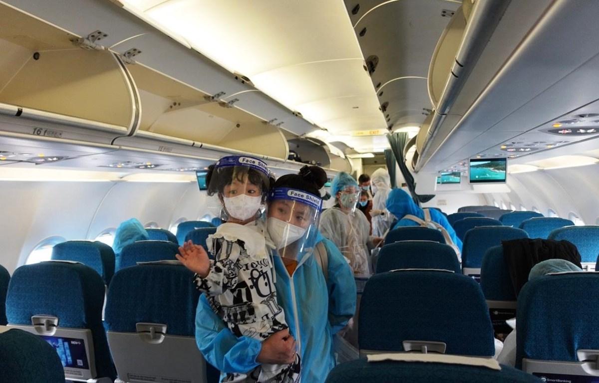 Hành khách trên chuyến bay của Vietnam Airlines đưa 200 người dân Quảng Nam từ Thành phố Hồ Chí Minh hồi hương. (Ảnh: CTV/Vietnam+)