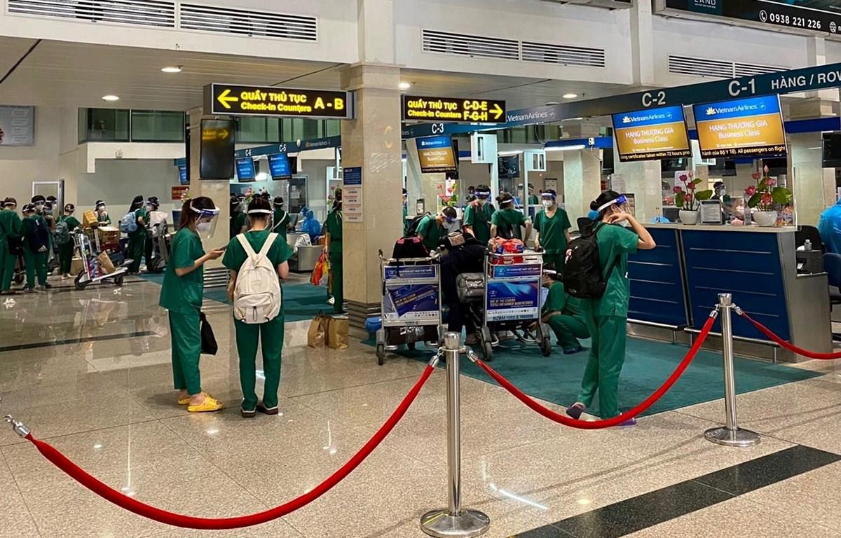 Đoàn y bác sỹ làm thủ tục tại sân bay Tân Sơn Nhất. (Ảnh: CTV/Vietnam+)