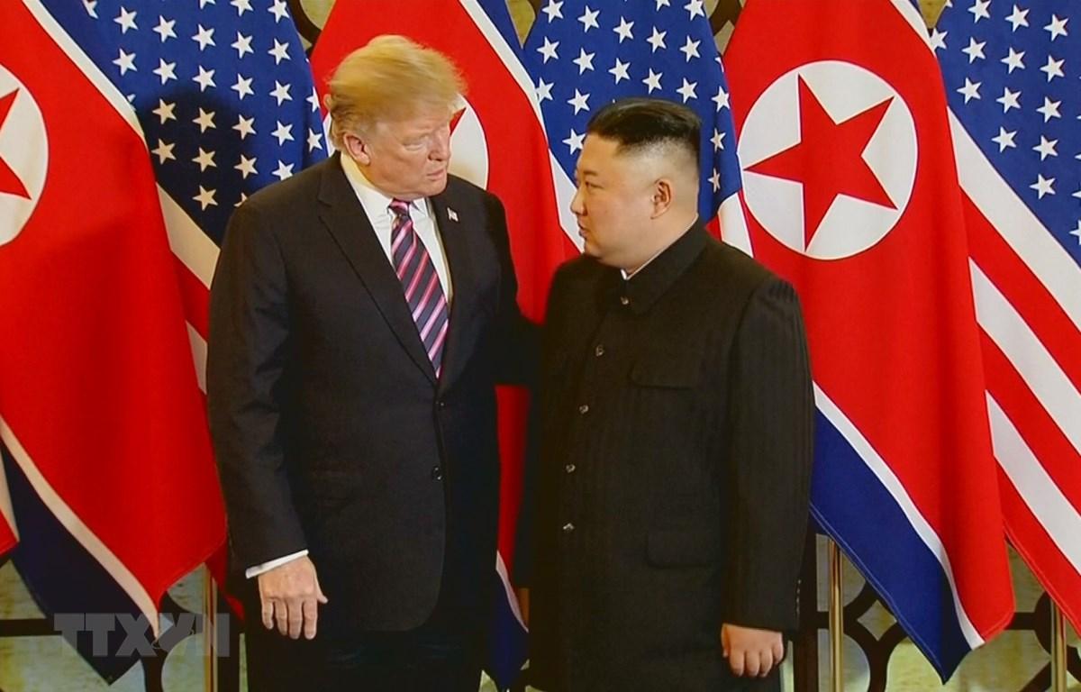 Tổng thống Mỹ Donald Trump và Chủ tịch Triều Tiên Kim Jong-un trao đổi ngắn sau khi bắt tay nhau với biểu cảm khá thân thiện ngày 27/2. (Ảnh: TTXVN)