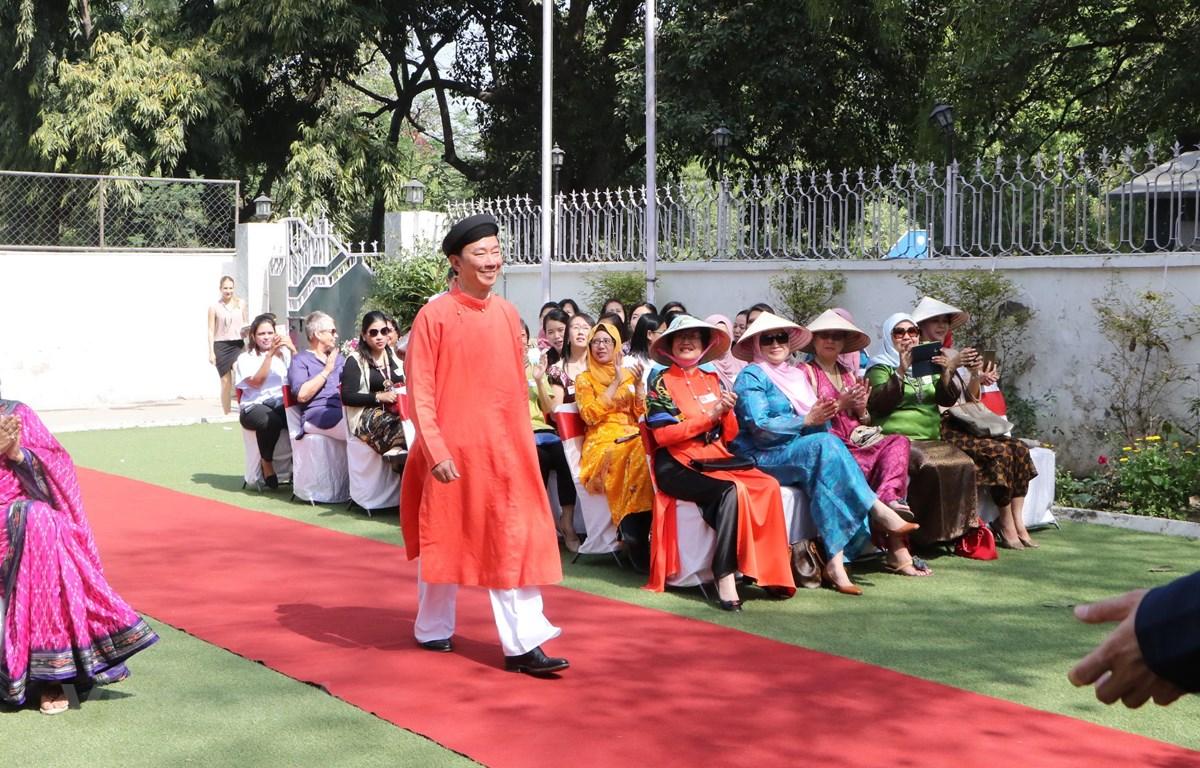 Đại sứ Phạm Sanh Châu trình diễn áo dài nam. (Ảnh: Huy Lê/Vietnam+)