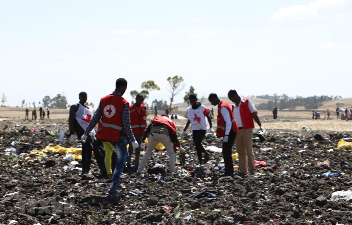Nhân viên Chữ Thập Đỏ dọn dẹp tại hiện trường vụ tai nạn máy bay của hãng hàng không Ethiopia Airlines tại Bishoftu, Ethiopia. (Ảnh: AFP/TTXVN)