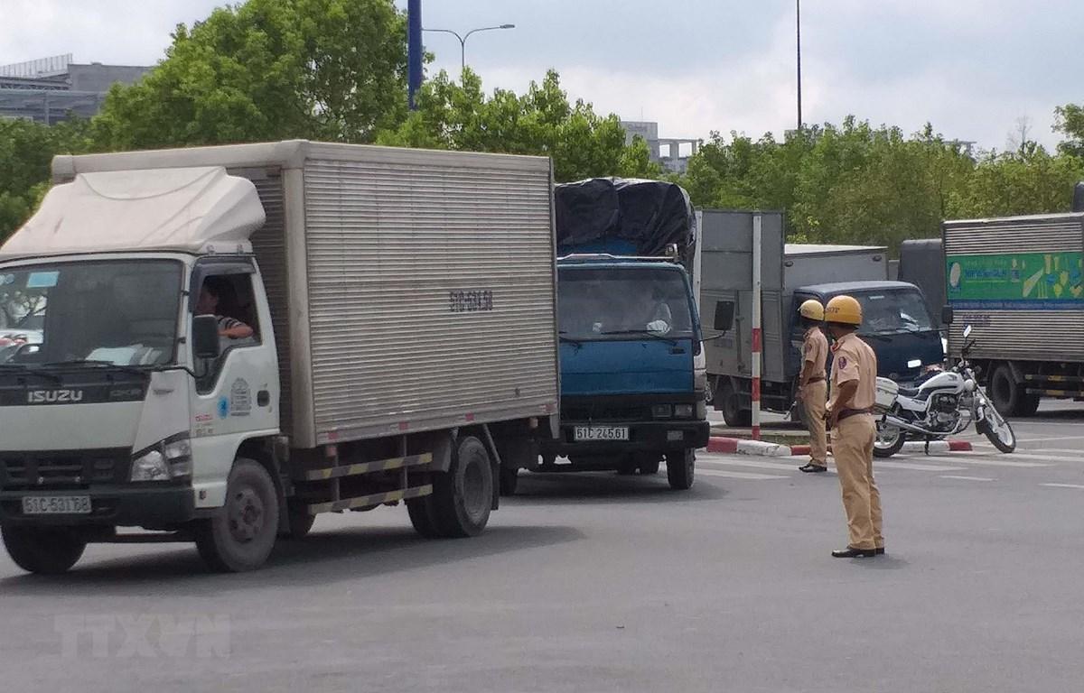 Cảnh sát giao thông Cát Lái (Thành phố Hồ Chí Minh) điều tiết các phương tiện tránh vào hầm vượt sông Sài Gòn. (Ảnh: Hoàng Hải/TTXVN)