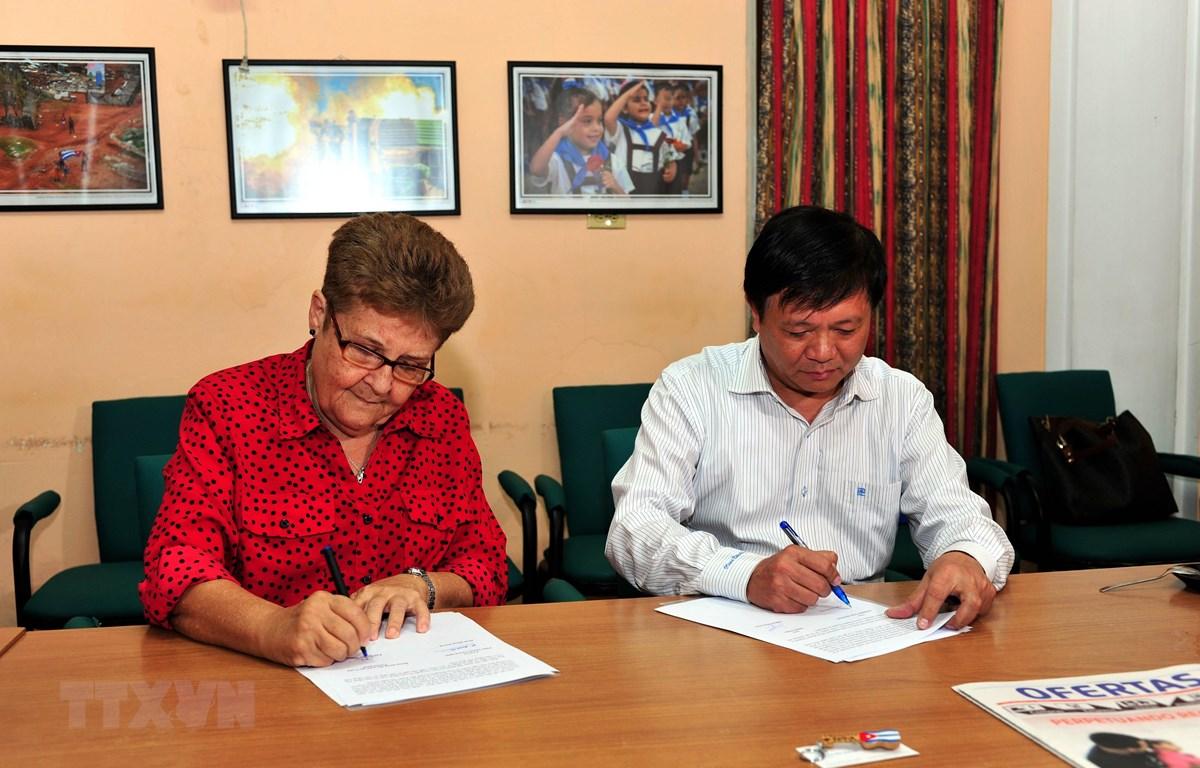 Phó Tổng giám đốc TTXVN Đinh Đăng Quang và Giám đốc Cuba ACN Edda Diz Garcés ký kết biên bản bàn giao trang thiết bị tác nghiệp. (Ảnh: Vũ Lê Hà/TTXVN)