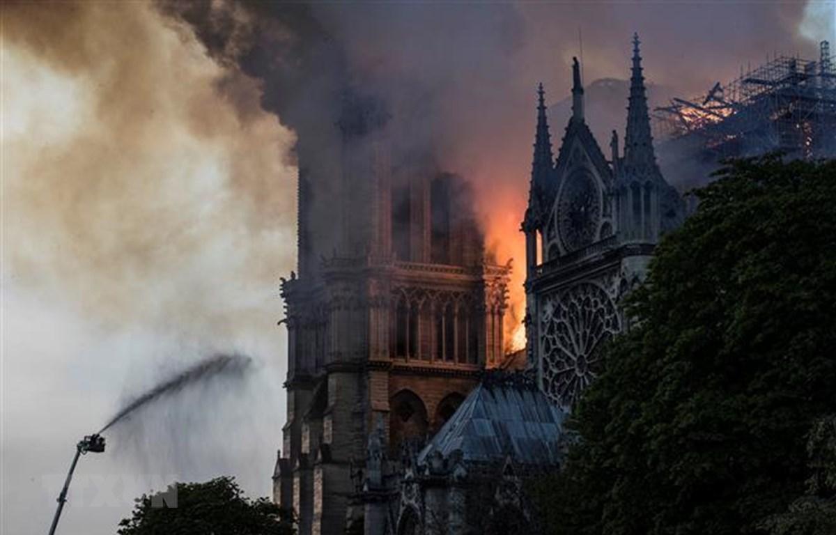 Lửa khói bốc lên dữ dội trên nóc nhà thờ Đức Bà ở Paris, Pháp ngày 15/4/2019. (Ảnh: AFP/TTXVN)