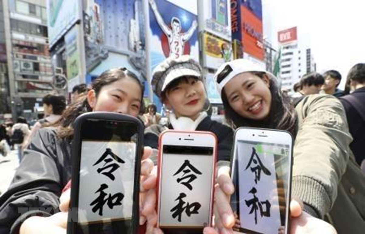 Các cô gái giới thiệu tên niên hiệu mới của Nhật Bản trên màn hình điện thoại ở Osaka ngày 1/4. (Ảnh: Kyodo/TTXVN)