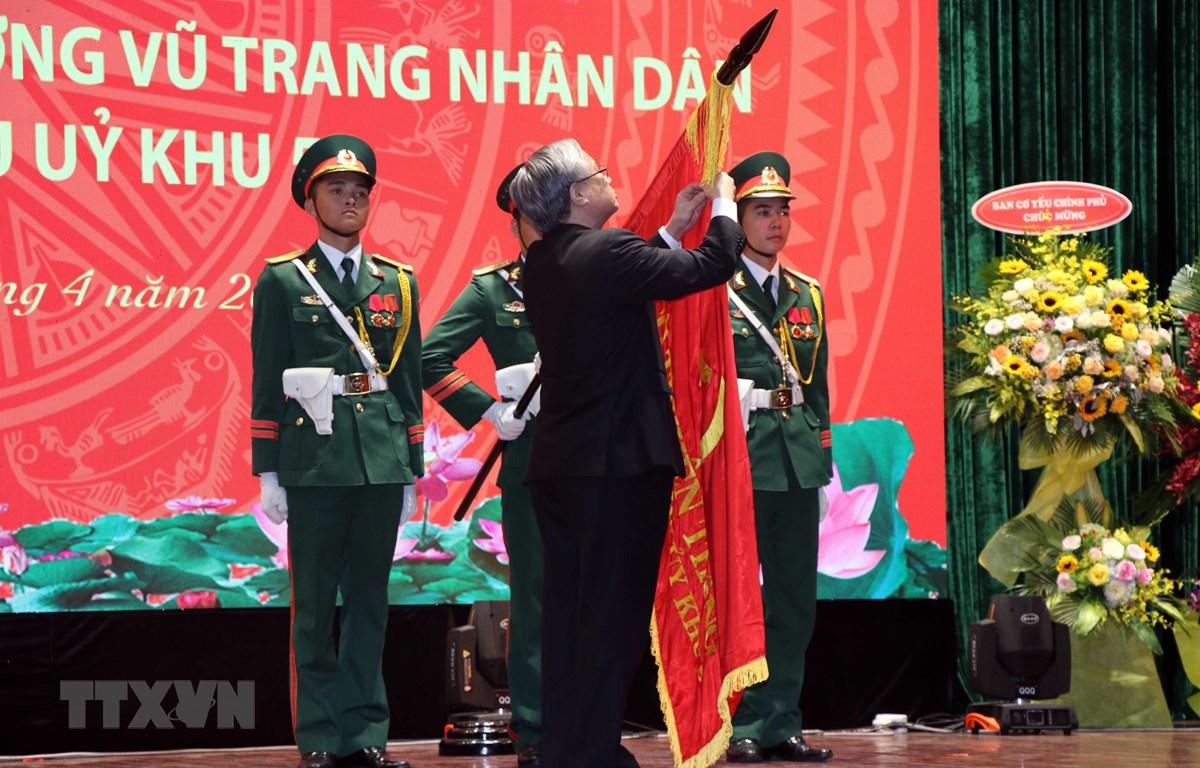 Thường trực Ban Bí thư Trần Quốc Vượng gắn danh hiệu Anh hùng Lực lượng vũ trang nhân dân lên Cờ truyền thống của Văn phòng Khu ủy Khu 5. (Ảnh: Nguyễn Sơn-TTXVN)