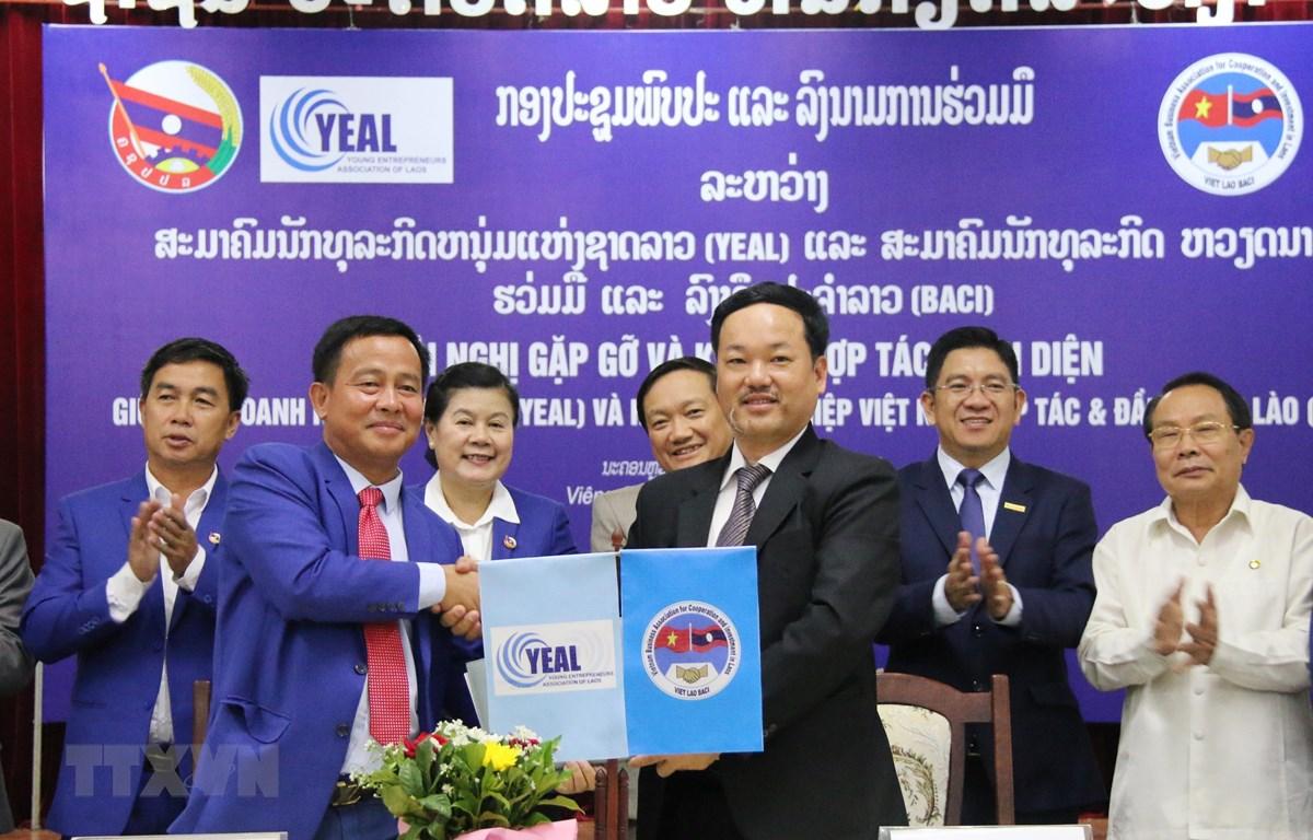 Chủ tịch BACI Nguyễn Thế Hiền (phải) và Chủ tịch YEAL Khamsen Sisavong trao văn kiện ký kết hợp tác. Ảnh: Xuân Tú/TTXVN)