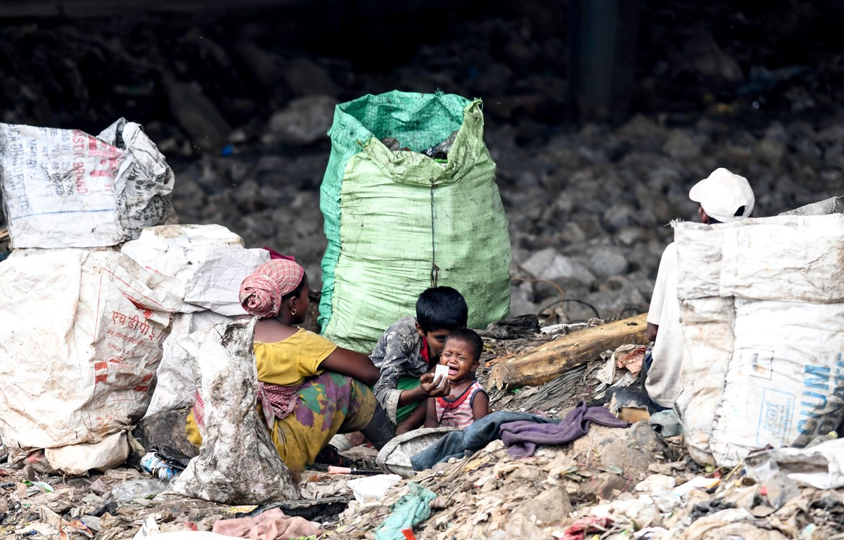 Một bà mẹ cùng các con nhặt rác tái chế tại Guwahati, Ấn Độ. (Ảnh: AFP/TTXVN)
