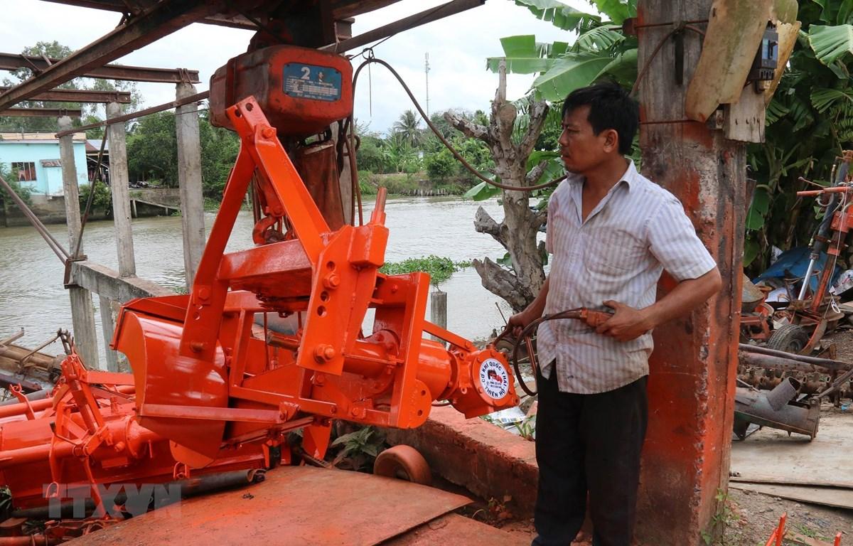 Ông Dương Quốc Thái vận hành thử máy đắp bờ. (Ảnh: Minh Trí-TTXVN)