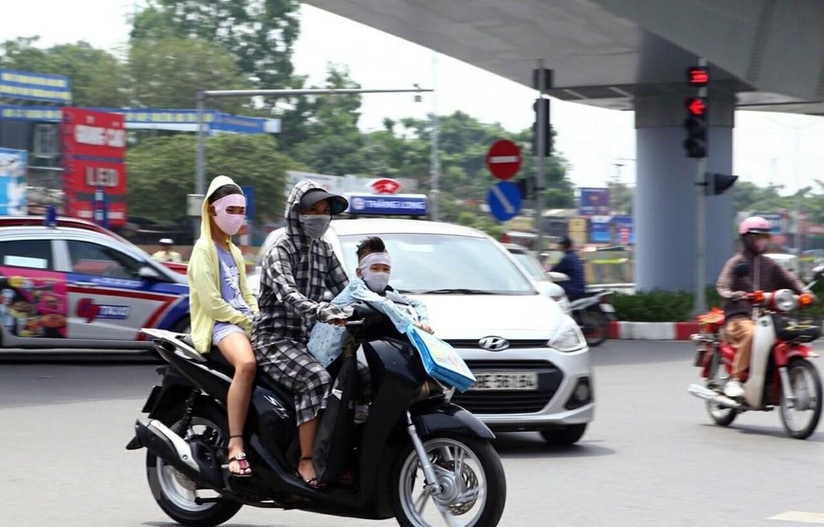 Nếu có việc phải ra ngoài đường, cần trang phục bịt kín để chống tia UV có hại trong ánh nắng gay gắt. (Ảnh: Danh Lam/TTXVN)