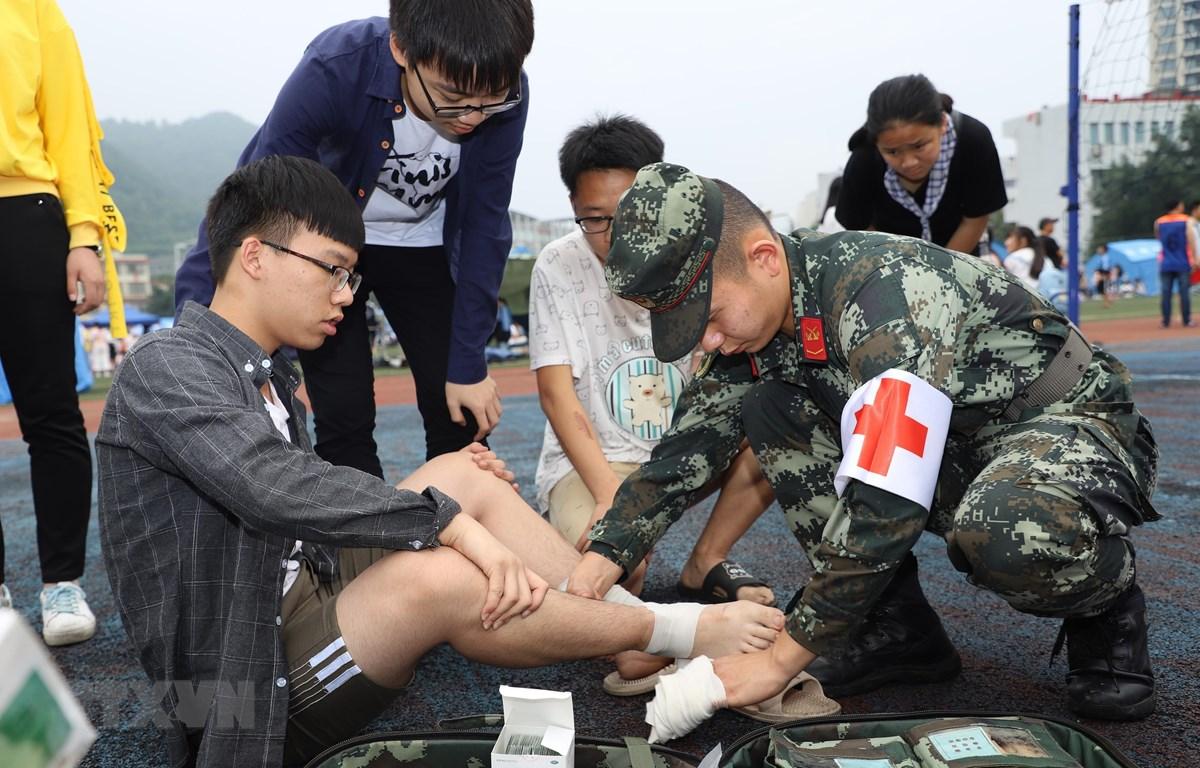 Binh sỹ Trung Quốc giúp đỡ người bị thương sau trận động đất ở Nghi Tân, tỉnh Tứ Xuyên, Trung Quốc ngày 18/6. (Ảnh: THX/TTXVN)