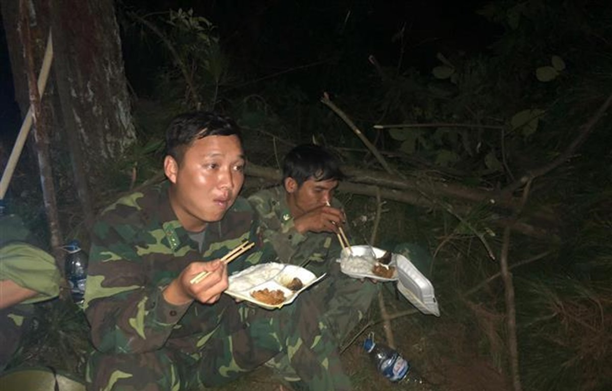 Bữa cơm vội tại chỗ của các lực lượng tham gia chữa cháy. (Ảnh Vũ Ngà/TTXVN)