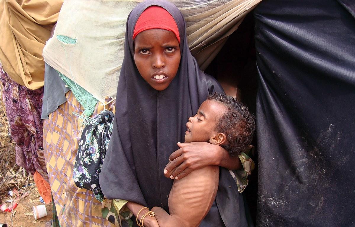 Một người mẹ trẻ bế đứa con suy dinh dưỡng tại một trung tâm y tế ở phia nam thủ đô Mogadishu, Somalia. (Ảnh: AFP/TTXVN)