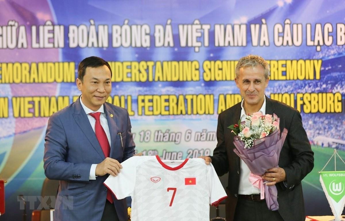 Ông Trần Quốc Tuấn; Phó Chủ tịch thường trực VFF (trái) tặng áo đấu của Đội tuyển Việt Nam cho ông Pierre Michael Littbarski, huyền thoại bóng đá Đức, Đại sứ CLB Wolfsburg. (Ảnh: Trọng Đạt/TTXVN)