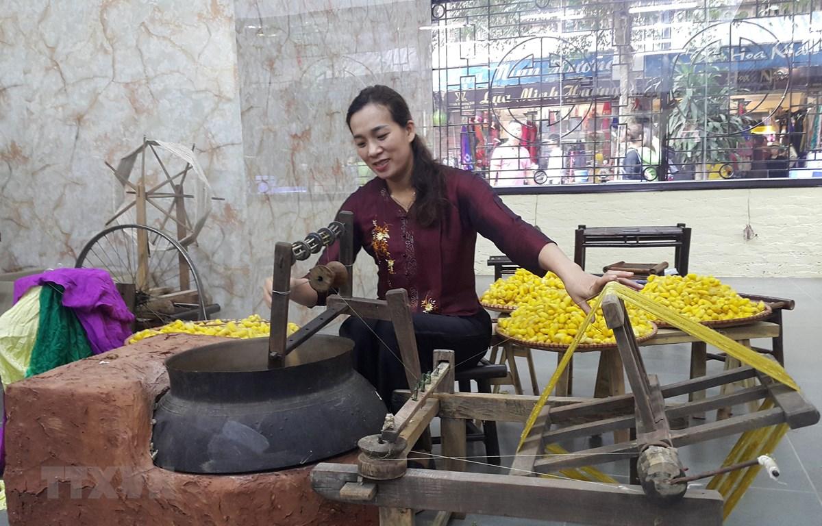Kéo tơ tằm dệt lụa tại làng nghề Vạn Phúc, Hà Nội. (Ảnh: Đinh Thuận/TTXVN)
