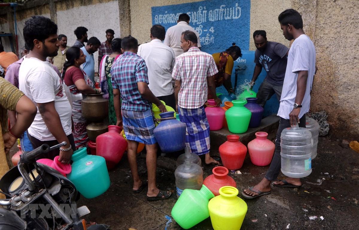 Người dân xếp hàng chờ lấy nước sinh hoạt tại Chennai, Ấn Độ ngày 25/6. (Ảnh: THX/TTXVN)