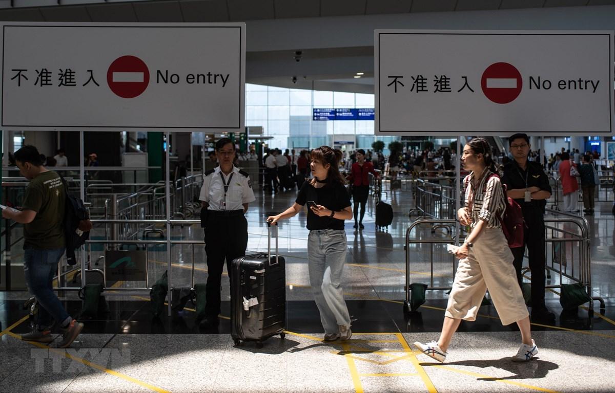 Hành khách làm thủ tục tại sân bay quốc tế Hong Kong ngày 14/8. (Ảnh: AFP/TTXVN)