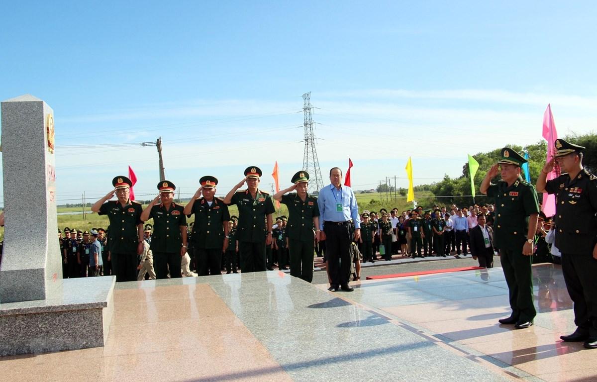 Đại biểu lãnh đạo Bộ Quốc phòng hai nước Việt Nam-Campuchia thực hiện nghi thức Lễ chào cờ cột mốc chủ quyền quốc gia tại cột mốc 275 - cửa khẩu quốc tế Tịnh Biên. (Ảnh: Công Mạo-TTXVN)
