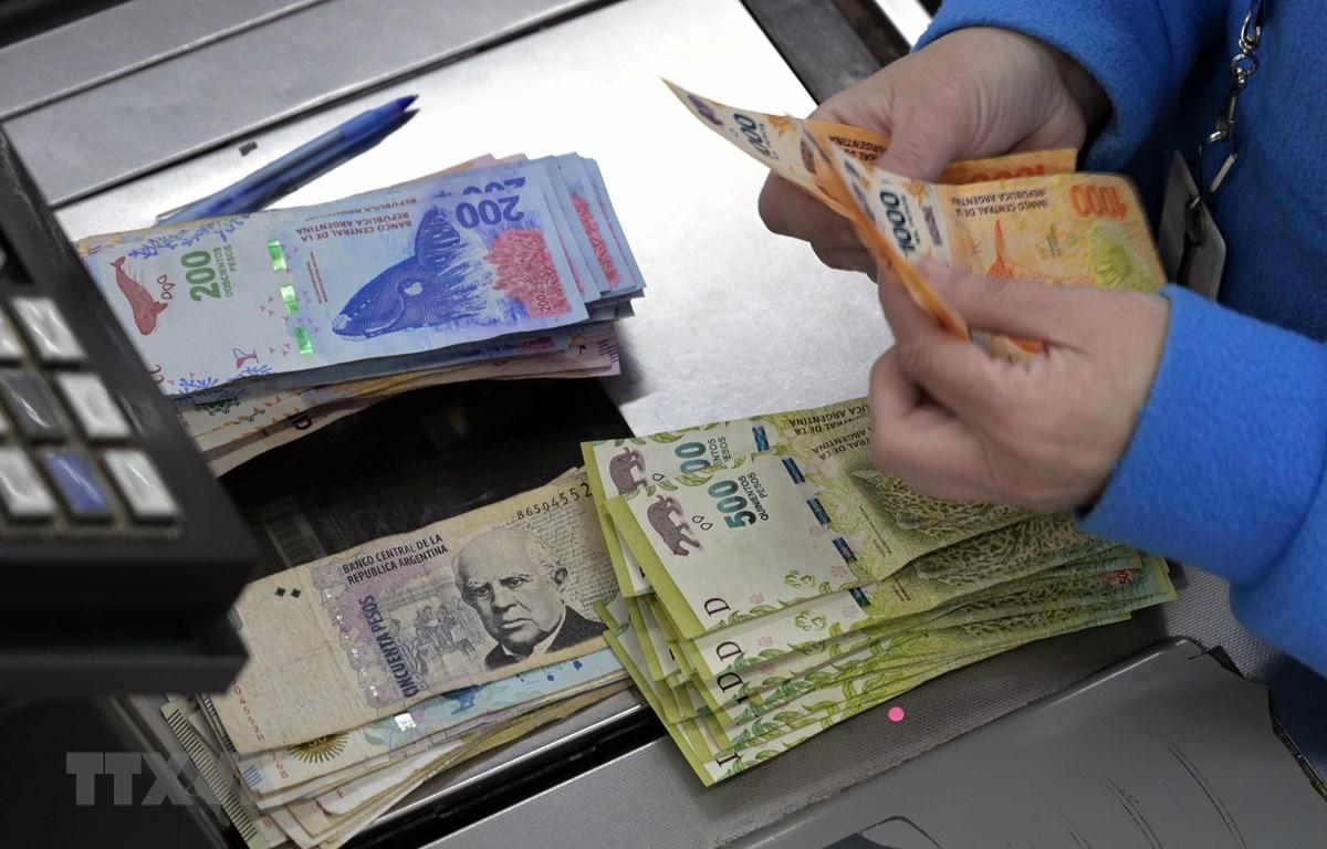 Kiểm đồng peso của Argentina tại một siêu thị ở Buenos Aires, ngày 15/8. (Ảnh: AFP/TTXVN)