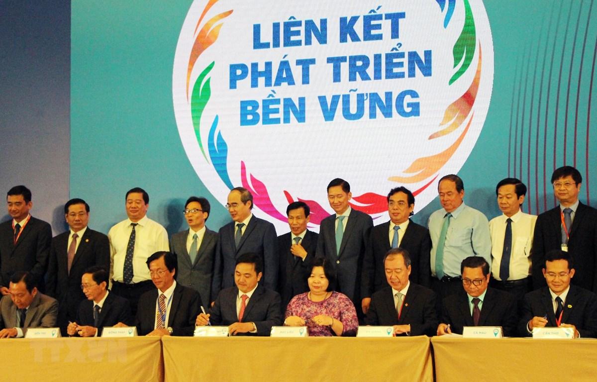 Đại diện thành phố Hồ Chí Minh và 13 tỉnh, thành khu vực Đồng bằng sông Cửu Long ký kết Chương trình hợp tác liên kết phát triển du lịch. (Ảnh: Mỹ Phương/TTXVN)