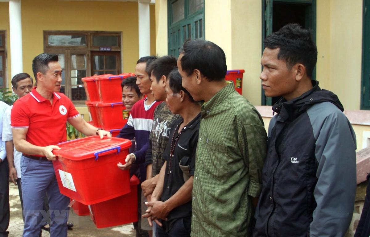 Ông Nguyễn Hải Anh - Phó Chủ tịch, Tổng Thư ký Hội Chữ thập đỏ Việt Nam trao tặng thùng đồ dùng gia đình cho các hộ gia đình. (Ảnh: Trịnh Bang Nhiệm/TTXVN)