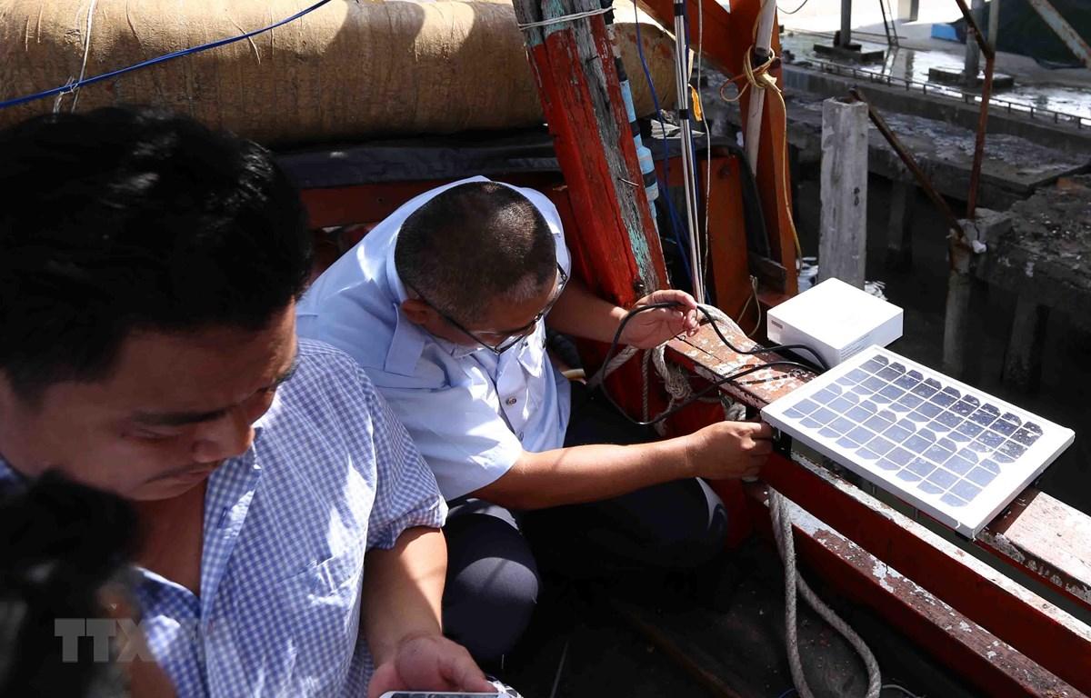 Thanh tra ngành thủy sản kiểm tra thiết bị giám sát hành trình khai thác thủy hải sản lắp đặt trên tàu cá của ngư dân. (Ảnh: Vũ Sinh/TTXVN)