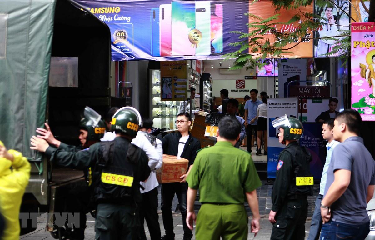 Cảnh sát kiểm tra, khám xét và đưa các kiện hàng lên xe tại cửa hàng điện thoại Nhật Cường mobile ở 33 Lý Quốc Sư, Hà Nội. (Ảnh: Doãn Tấn/TTXVN)
