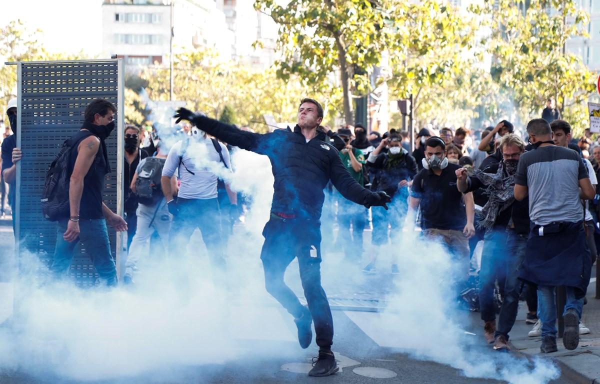 Người biểu tình bạo lực ném hơi cay trong cuộc tuần hành chống biến đổi khí hậu tại Paris, Pháp, ngày 21/9/2019. (Ảnh: AFP/TTXVN)