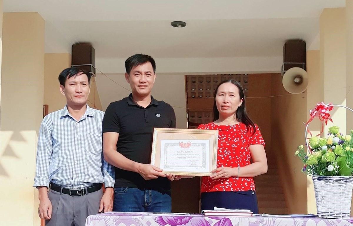Tặng Giấy khen thầy giáo Đồng Văn Nhân vì hành động dũng cảm cứu người. (Ảnh: Bích Huệ/TTXVN)
