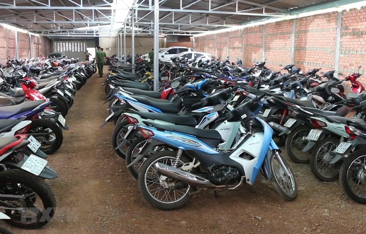 Lực lượng chức năng kiểm tra số xe máy trong các kho hàng của cơ sở cầm đồ. (Ảnh: Đậu Tất Thành/TTXVN)