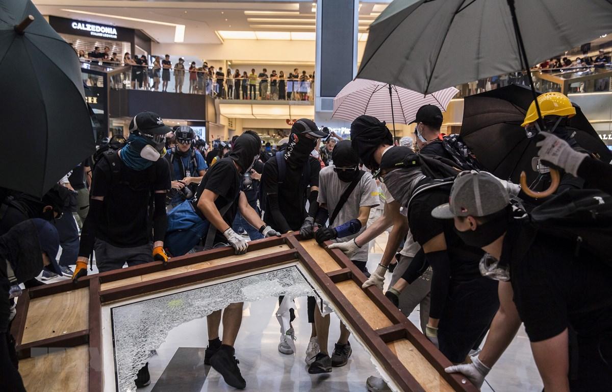 Người biểu tình quá khích che mặt phá hoại tại một trung tâm thương mại ở Sha Tin, Hong Kong ngày 22/9/2019. (Ảnh: AFP/TTXVN)