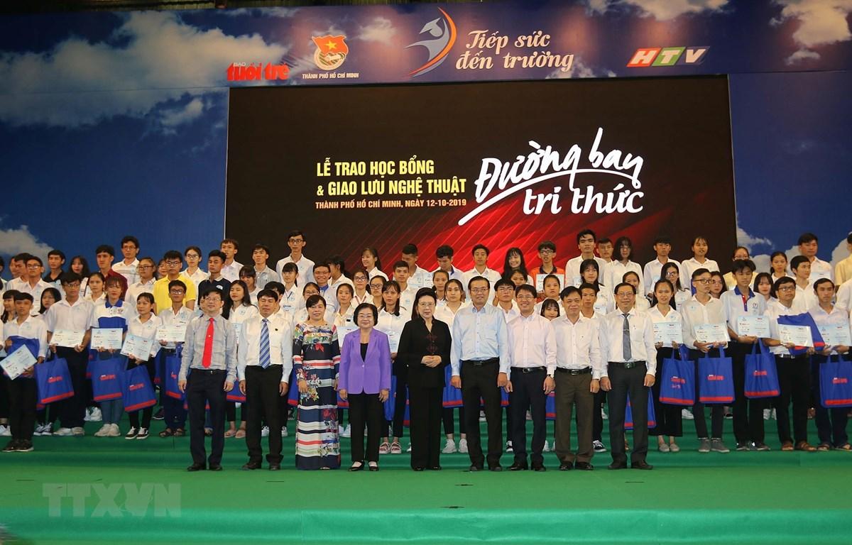 Lãnh đạo Thành phố, đại diện Ban tổ chức và các đơn vị tài trợ cùng các tân sinh viên nhận học bổng. (Ảnh: Thanh Vũ/ TTXVN)