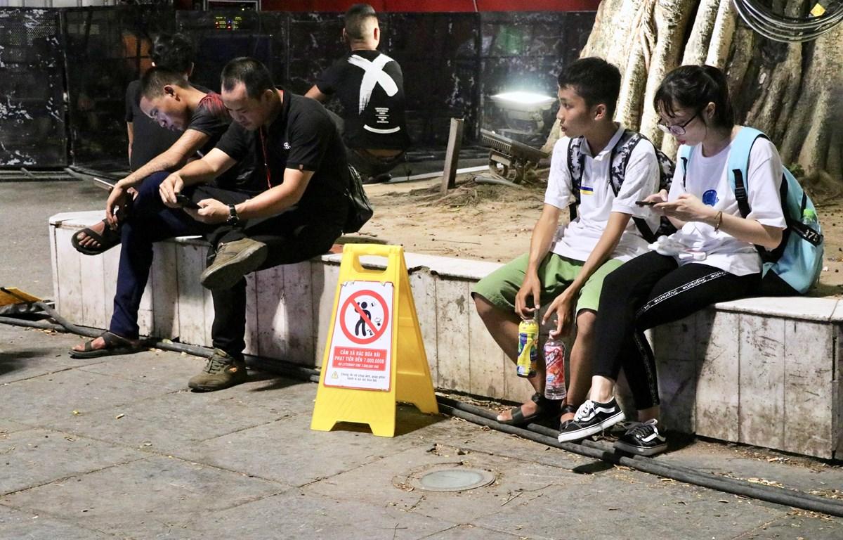 """Biển báo đặt ở phố đi bộ quận Hoàn Kiếm với nội dung """"Chúng tôi sẽ chụp ảnh, quay phim, hành vi xả rác bừa bãi. (Ảnh: Hồng Vĩ/TTXVN)"""
