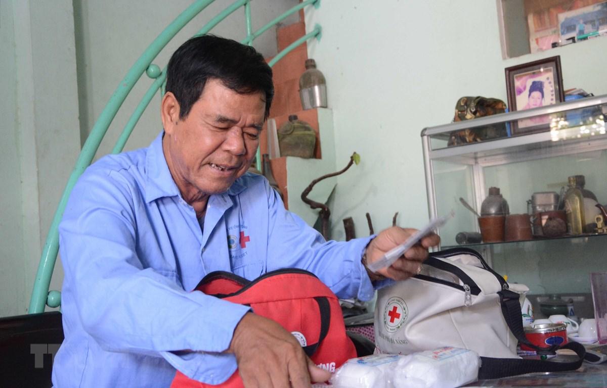 """Ông Đặng Thanh Kinh, thành viên của đội """"Xe ôm an toàn"""" thường xuyên kiểm tra túi sơ cứu. (Ảnh: Văn Dũng/TTXVN)"""