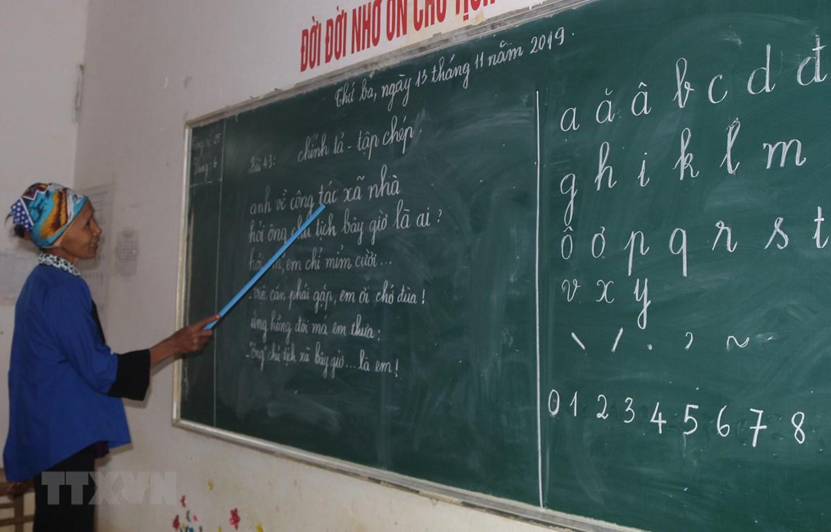 Đến lớp xóa mù chữ, người dân được luyện đọc những bài thơ ngắn. (Ảnh: Chu Hiệu/TTXVN)