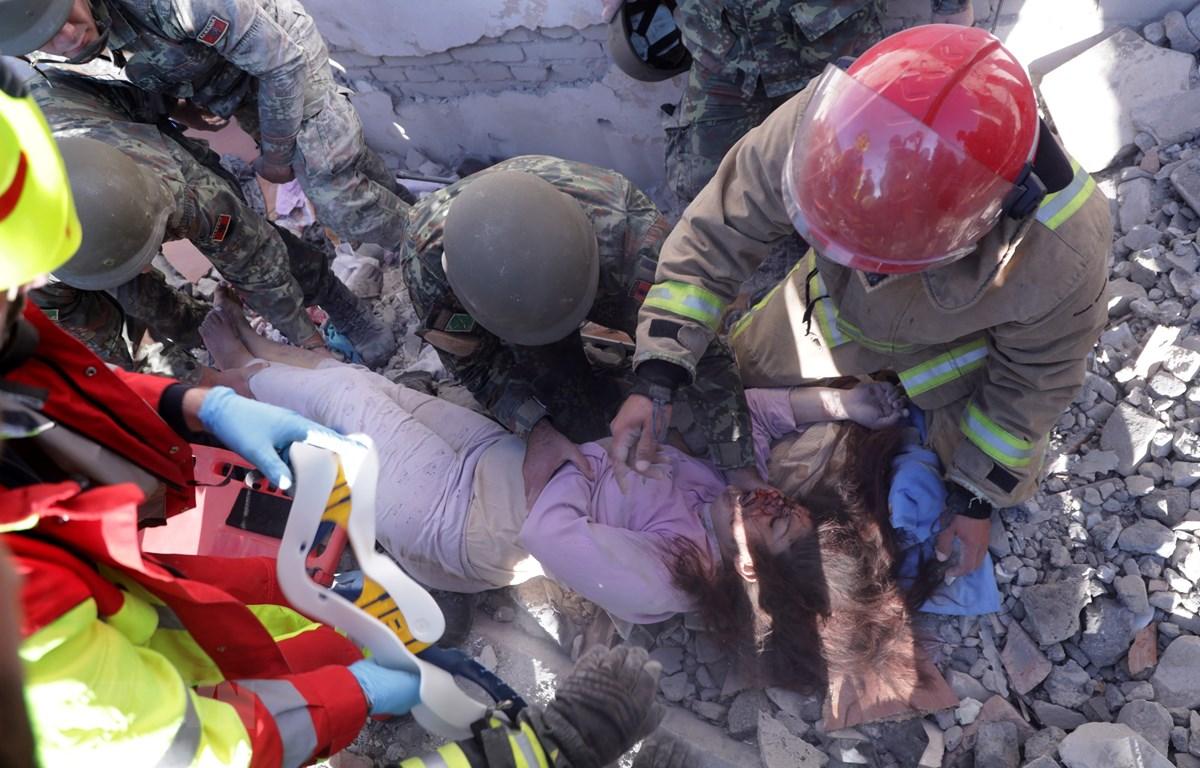 Lực lượng cứu hộ giải cứu nạn nhân mắc kẹt trong đống đổ nát sau trận động đất tại Thumane, Albania, ngày 26/11/2019. (Ảnh: AFP/TTXVN)
