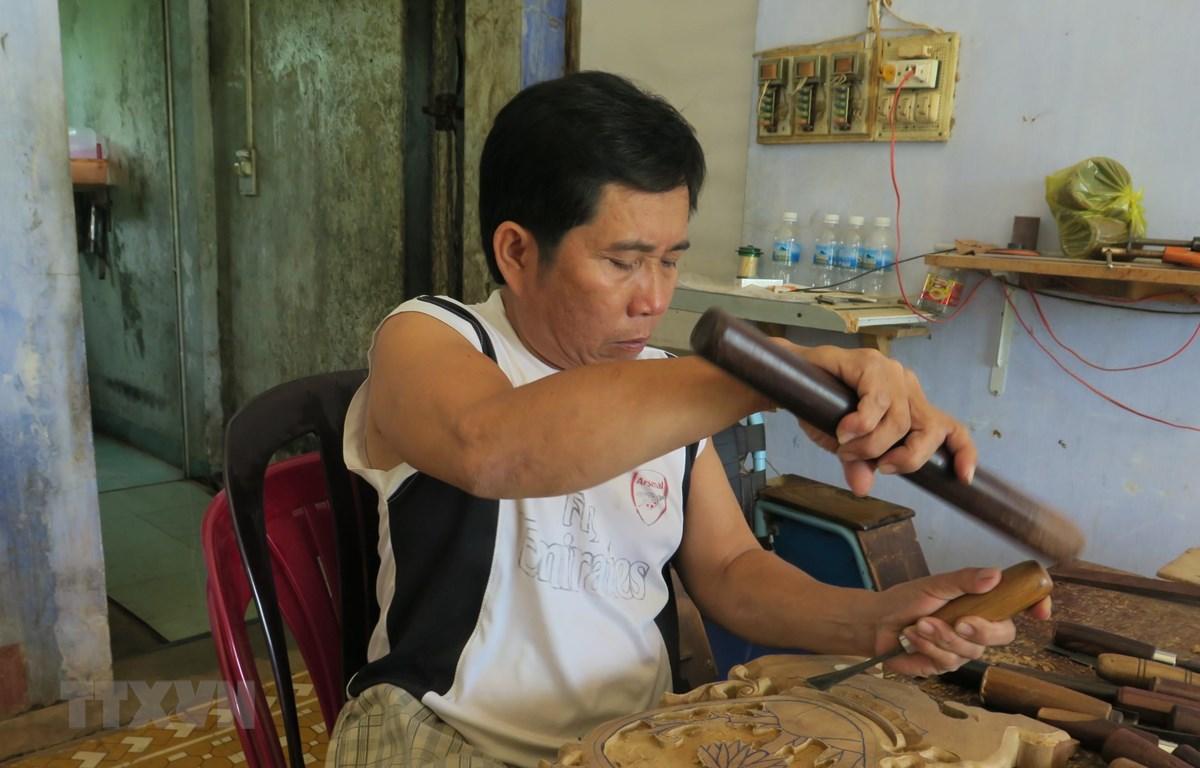Hội viên Lê Viết Luận, người khuyết tật, người thầy truyền nghề chạm khắc cho các hội viên Hội Người khuyết tật huyện Diên Khánh, Khánh Hòa. (Ảnh: Phan Sáu/TTXVN)