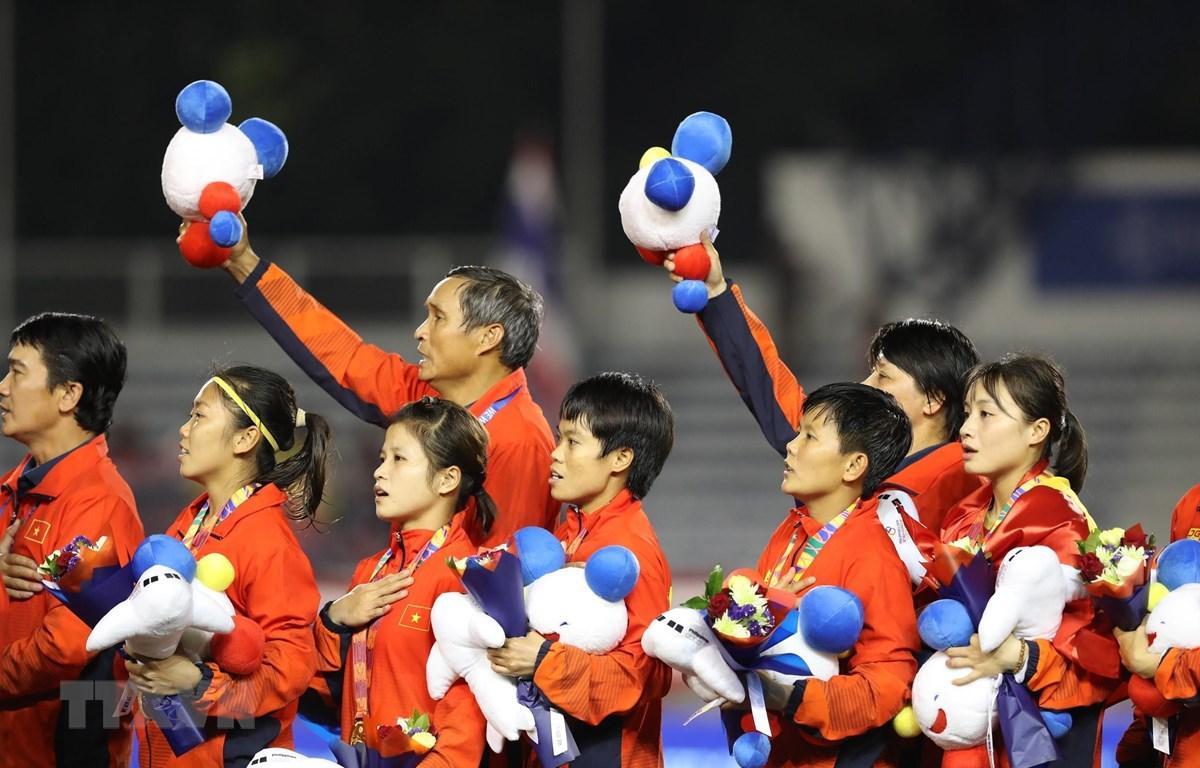 Đội tuyển nữ Việt Nam hát Quốc ca trên bục nhận huy chương. (Ảnh: Hoàng Linh/TTXVN)
