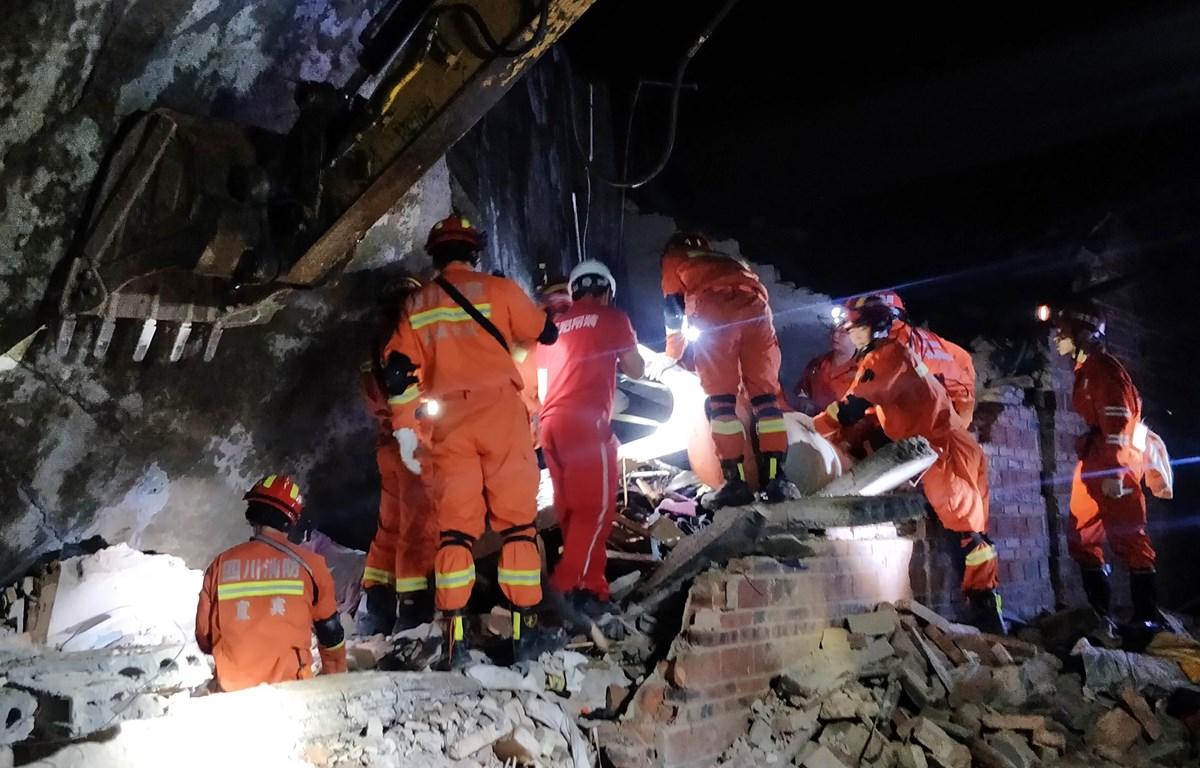 Lực lượng cứu hộ tìm kiếm nạn nhân dưới đống đổ nát của ngôi nhà bị đổ sập sau trận động đất ở tỉnh Tứ Xuyên, Trung Quốc, ngày 18/6/2019. (Ảnh: AFP/TTXVN)